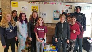 A group of students that assisting with collection of food for the food bank posed for a picture.