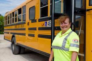 A female bus driver standing in front of a school bus with a big smile