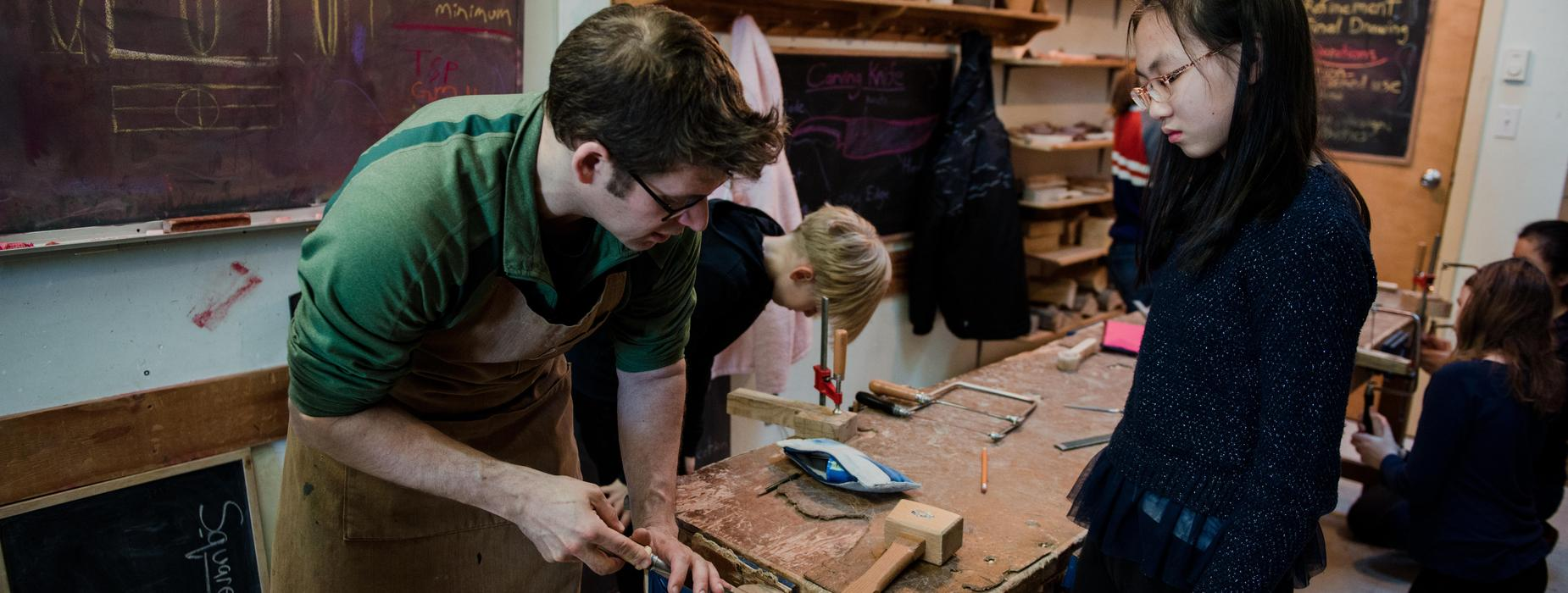 Photo of teacher and child in wood work shop