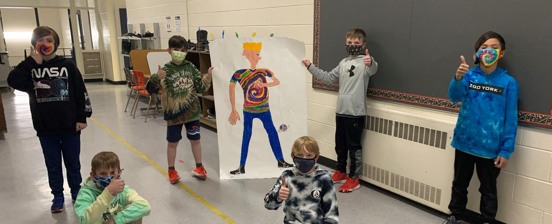6 male students from a Grade 4/5 class, posing in the hallway with 2 students holding a life-sized picture of the NED character.