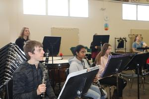 Students sitting in a row playing instruments at a concert