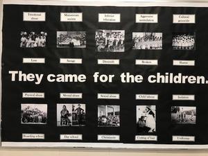 A black poster with multiple picture of children.  Wording reads, They came for the children.