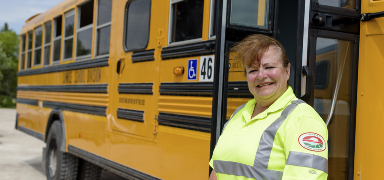 Bus driver in front of bus.