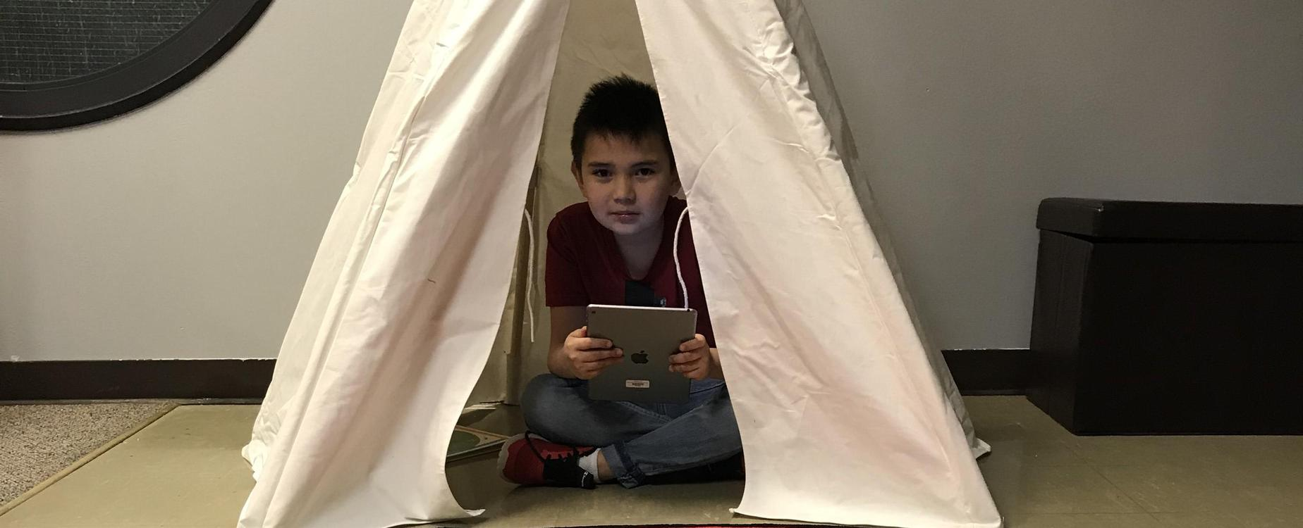 boy in a tent with an ipad