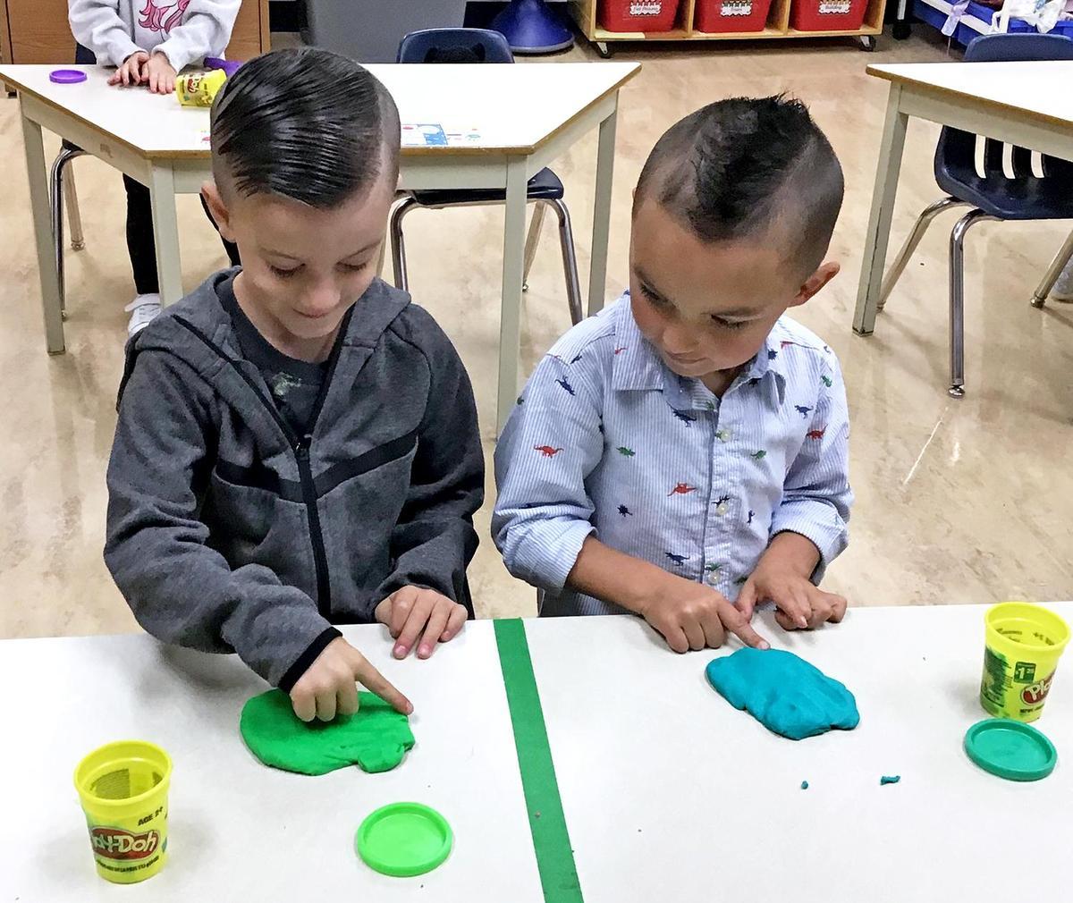 Two kindergarten boys playing with playdough