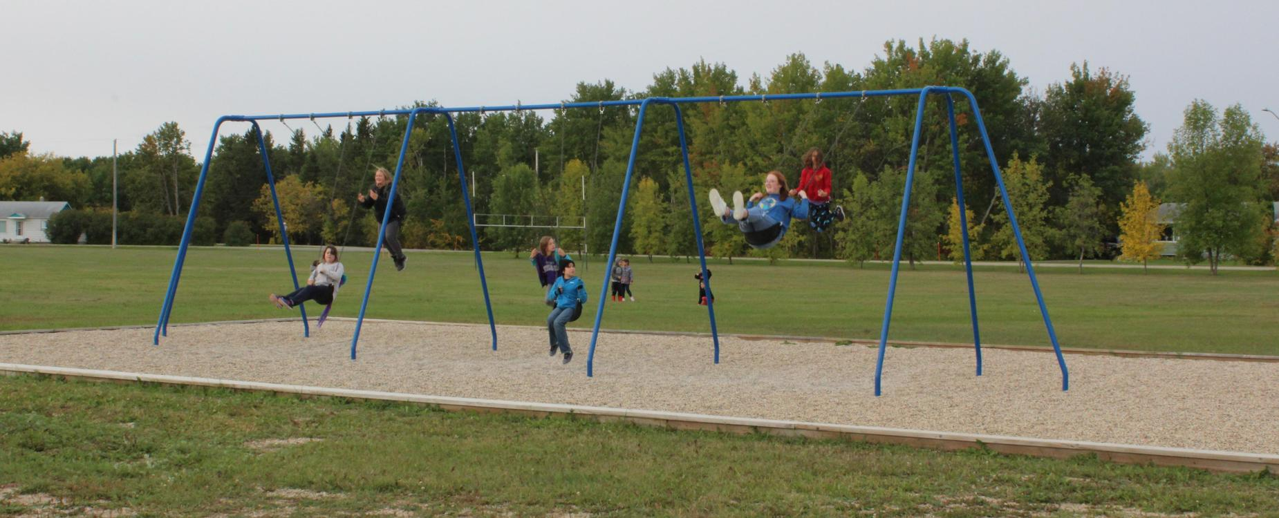 children on swing set in playground