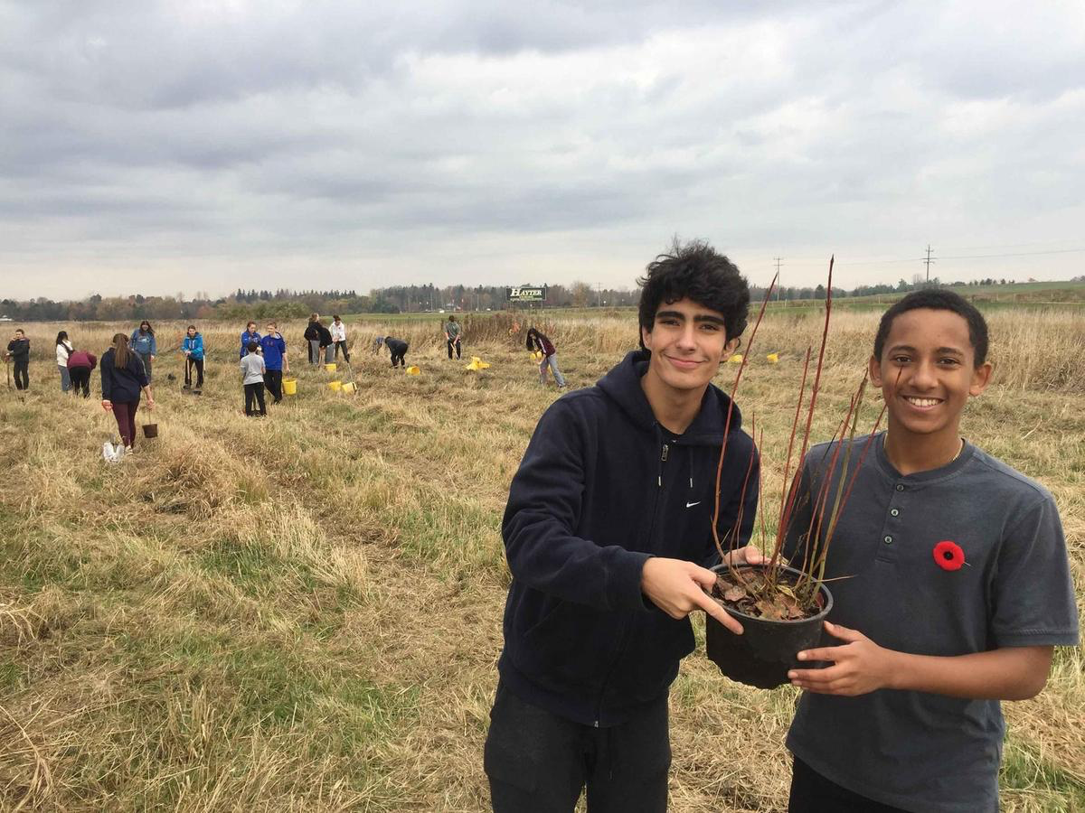 two male students holding a small plant in the field
