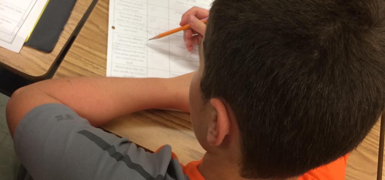 Student doing school work at desk.