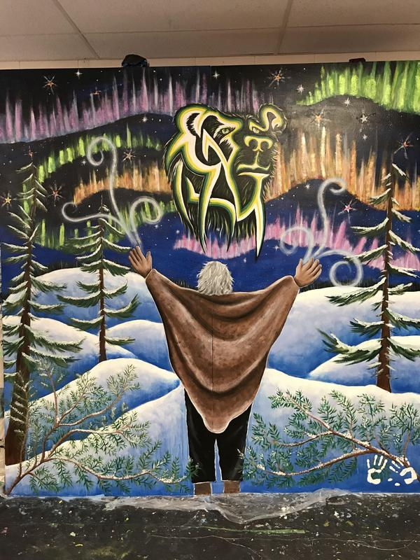 Mural with man standing in front of now hills with a blanket around him with this hands in the air