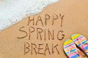 Beach scene with Happy Spring Break written in the sand beside flip flops