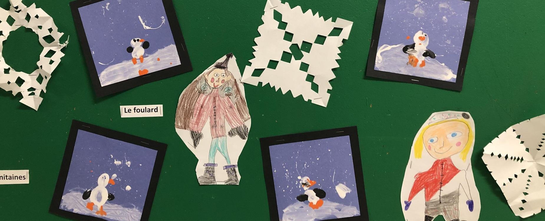 Painted pictures of penguins and cut out paper snowflakes, along with student drawings of themselves