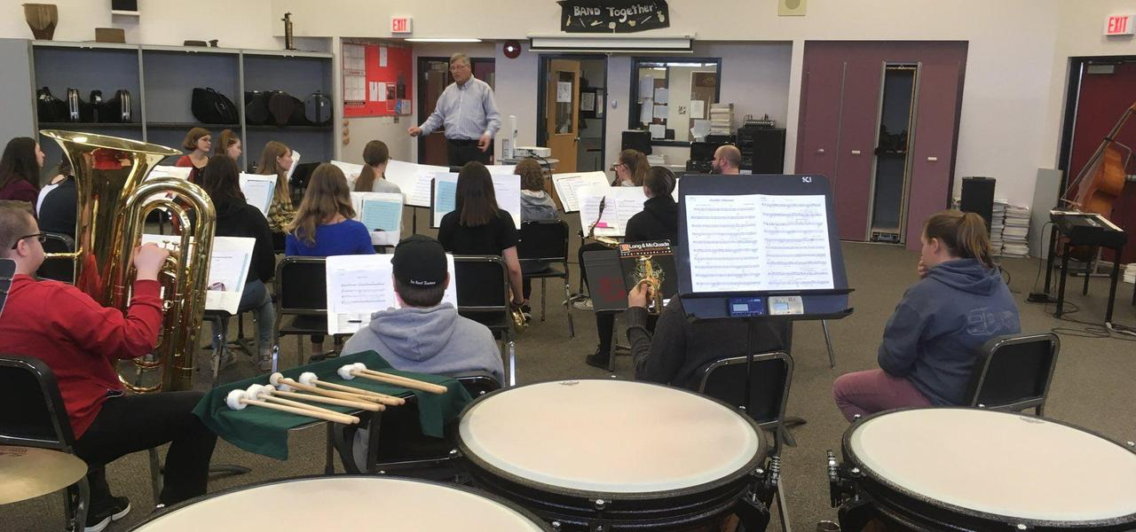 Students sitting in the band room practicing for an upcoming concert.  Teacher is giving instruction at the front of the class.