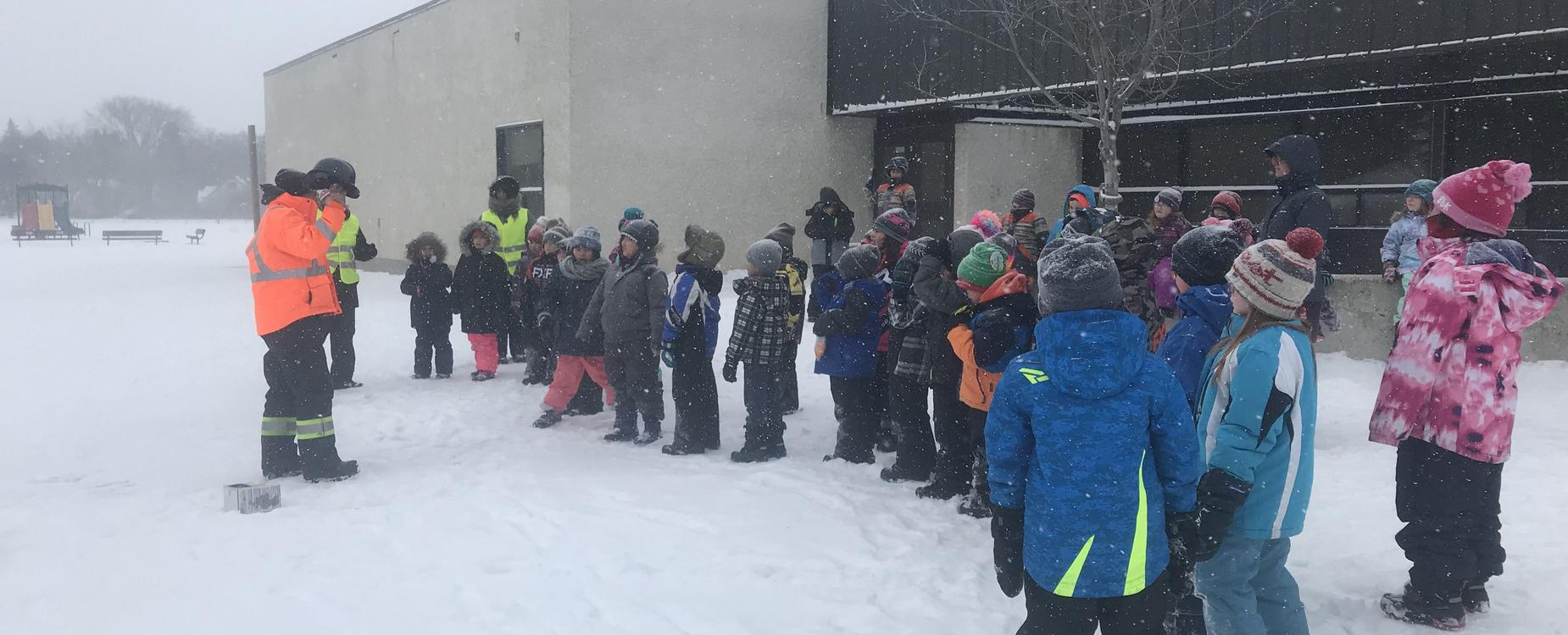 students standing outside in the snow learning about safety when operating equipment