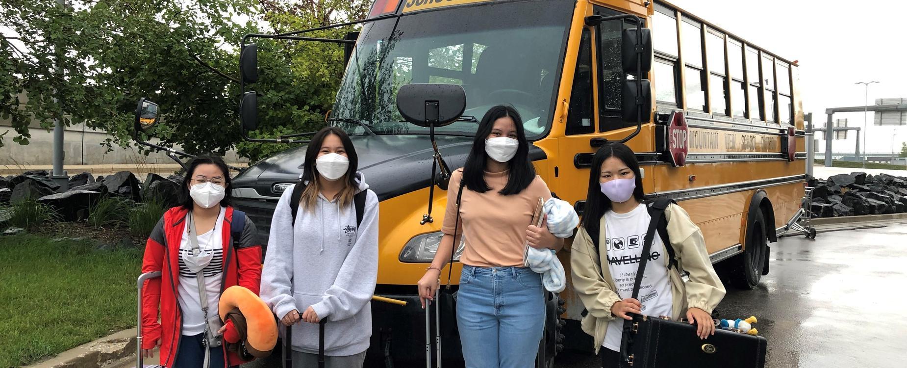 girls posing in front of school bus