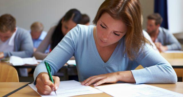 girl sitting at desk writing exam