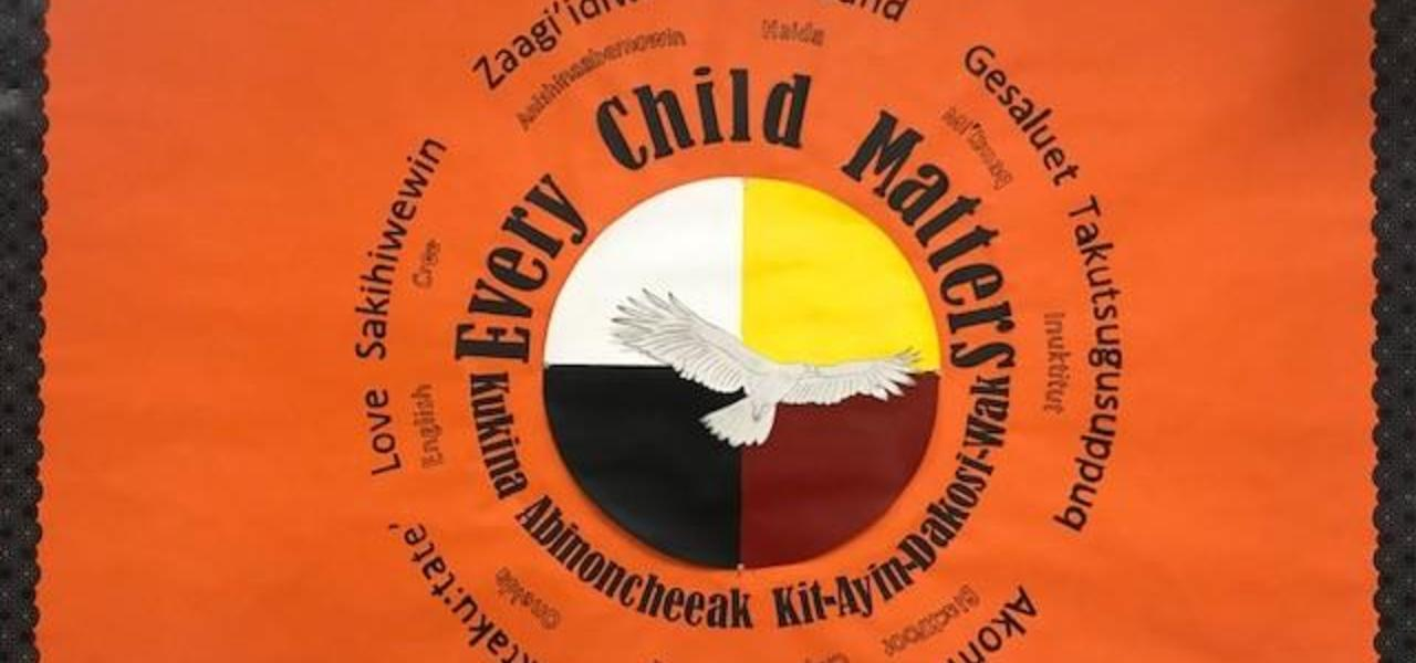 An orange poster that reads, Every Child Matters.  Also written in multiple languages.  Black poster surrounds the border.