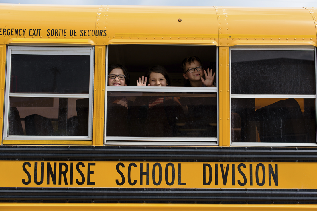 Kids waving through windows of bus.