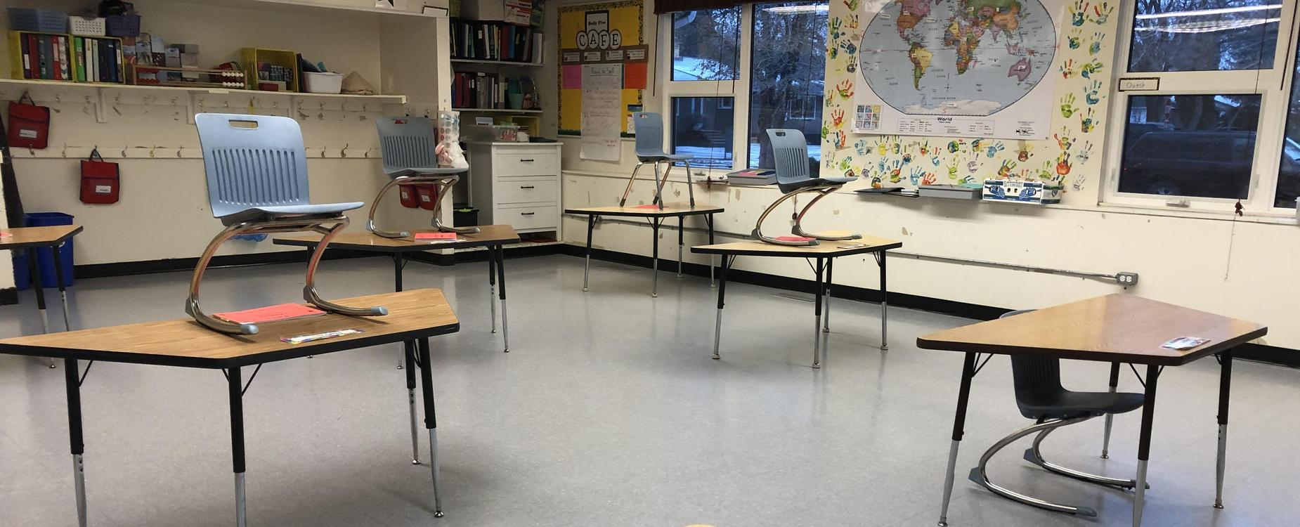 Pictures of school tables in a classroom, spaced far apart to allow for social distancing requirements.