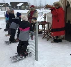 4 students dressed in winter closes, with skis on their feet, leaning up against a chain link fence watching a display by two voyageur staff.