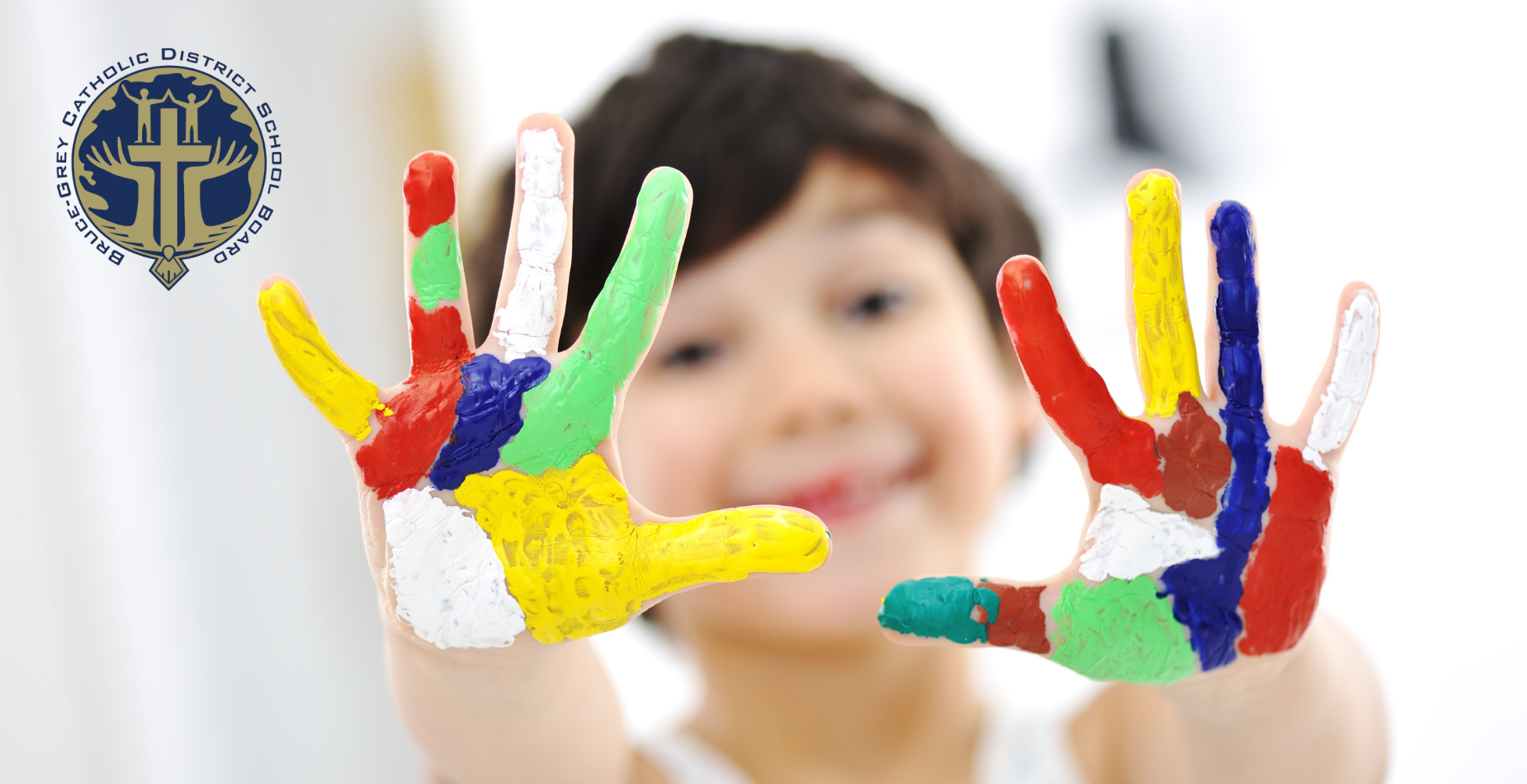 young child holding up hands covered in paint