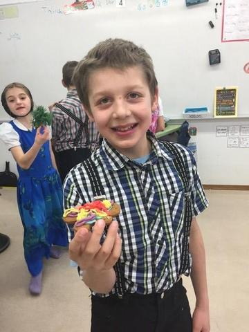 A male student smiling and holding a cupcake in his hand and a girl standing behind him.