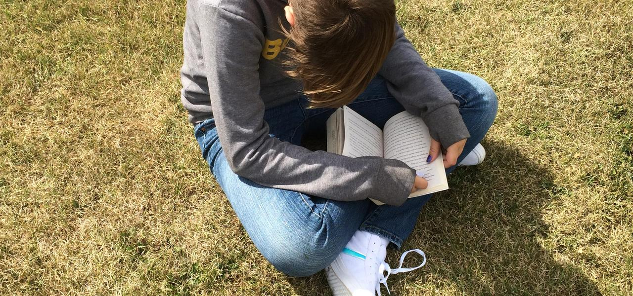 Student reading in the field