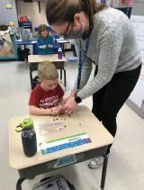 A teacher is working with students on craft projects at desks in school.