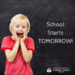 boy with chalkboard that says school starts tomorrow