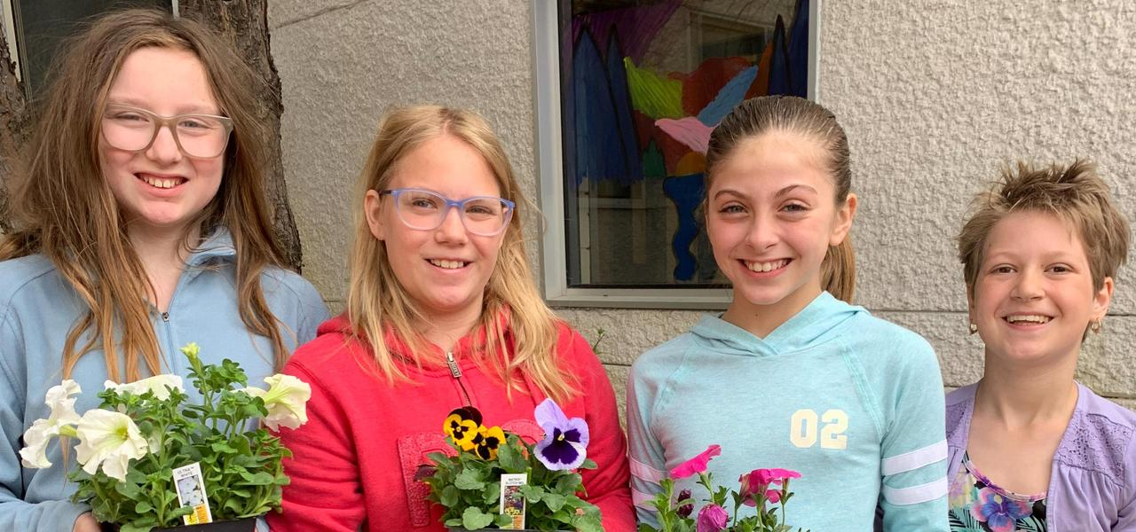 Four students holding flower pots
