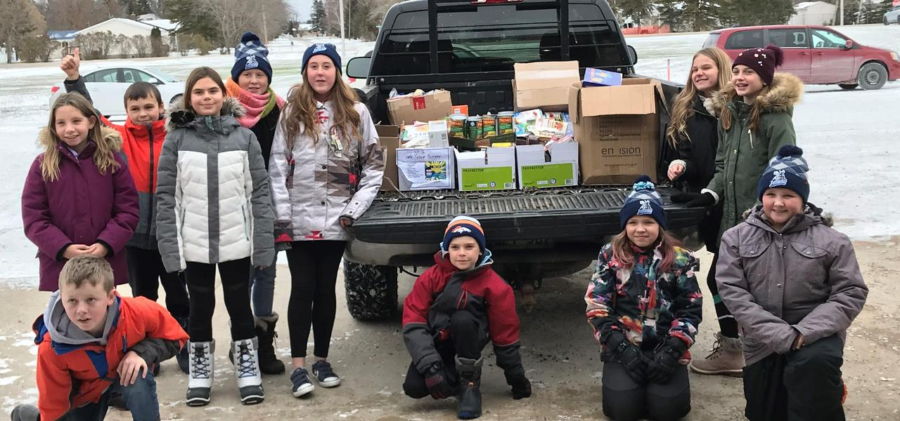 A group of Centennial School Student surround a truck that they have filled with boxes of food for the food bank.