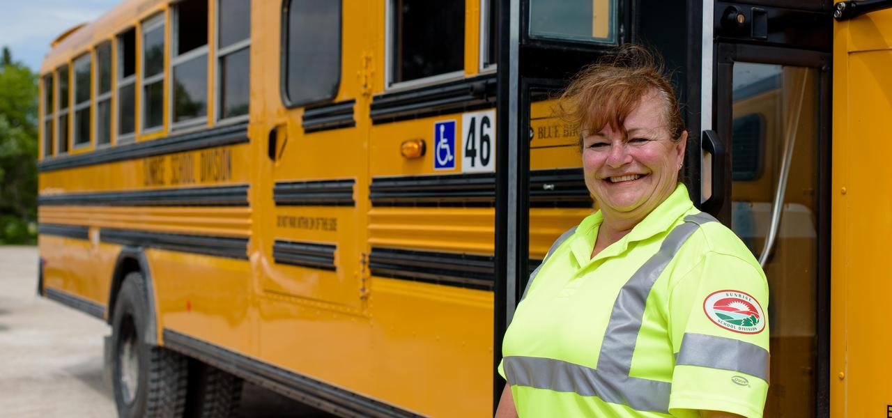 A female bus driver in a yellow high vis shirt standing in front of a school bus smiling.