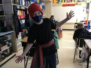 A student posing for  a picture wearing a long sache around waste and a red toque to look like a voyageur.