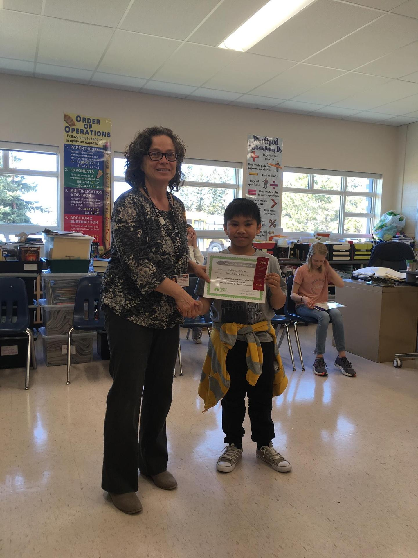 Mrs. Dienstbier presenting Harvey his 1st place ribbon.