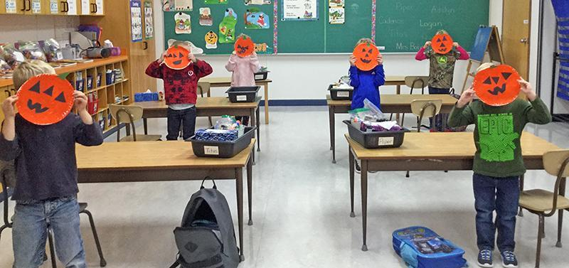 children with paper pumpkins covering their faces
