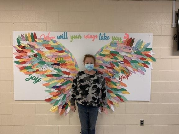 Person standing in front of student-made wings with message 'where will your wings take you?'