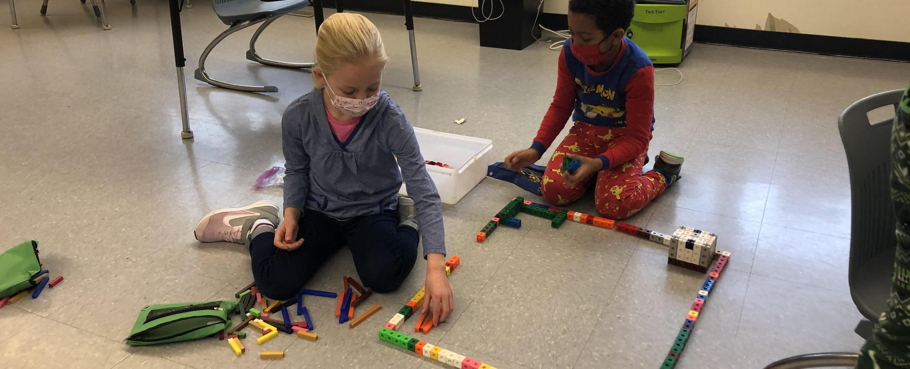 2 students are in the process of building their community using various wooden and plastic blocks.