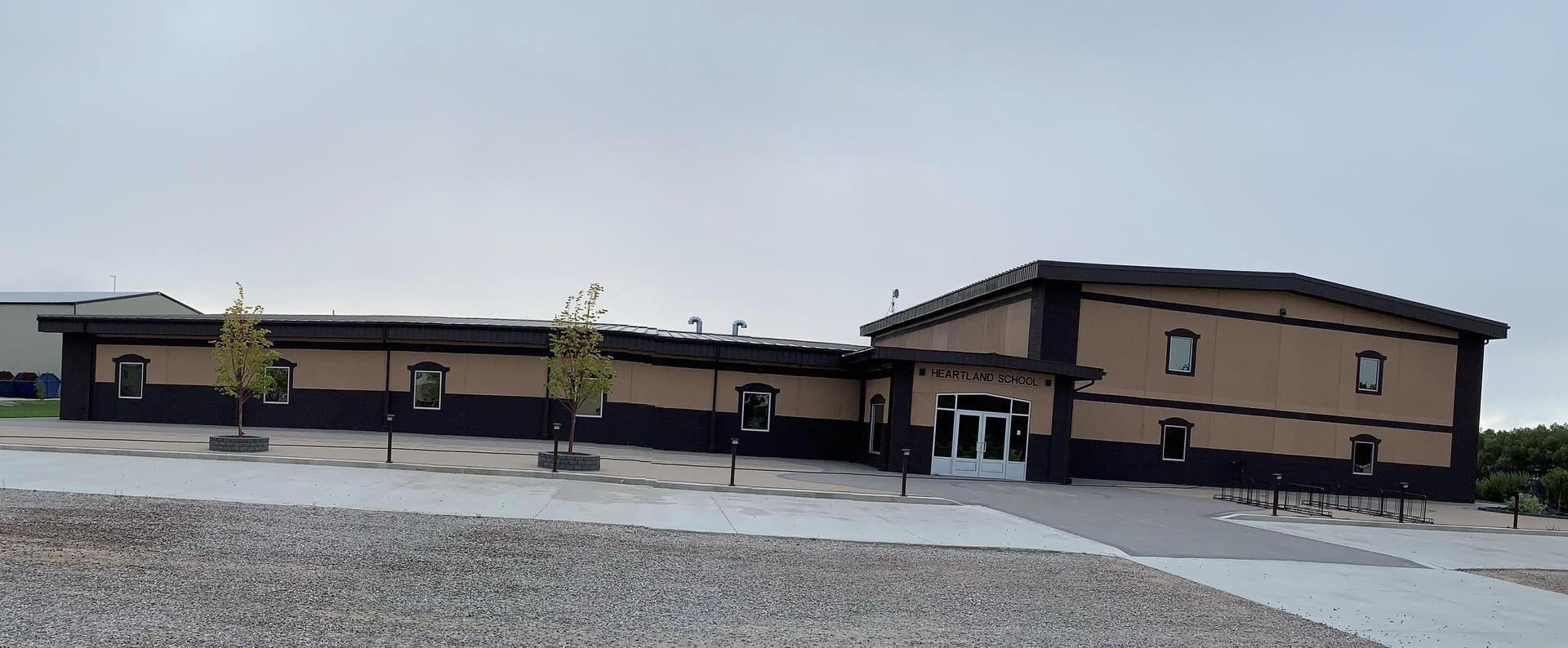 A picture of the exterior of Heartland School.  It is beige and brown with trees in front of the school.
