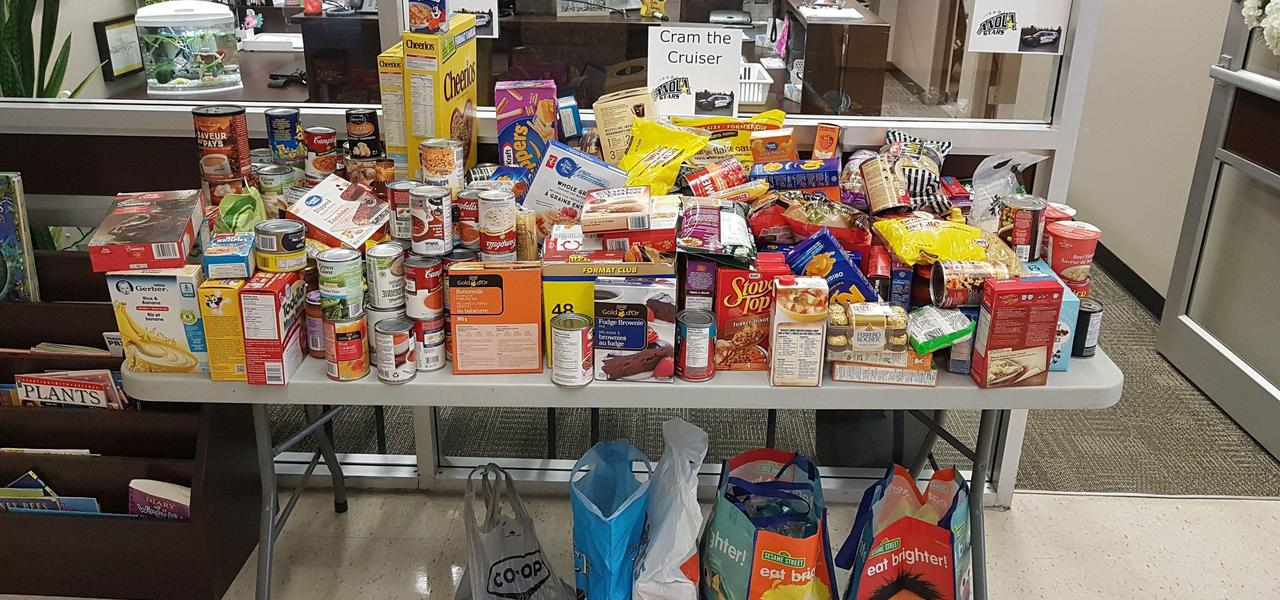 A large table full of food consisting of can goods, cereal, baby food, pasta and much more that will be donated to the food bank.