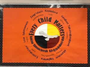 An orange poster that say Every Child Matter. Also written in multiple languages. Black border surrounds the poster