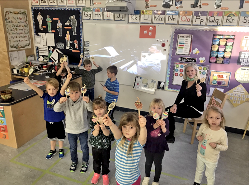 Kindergarten students showing off their stick puppets