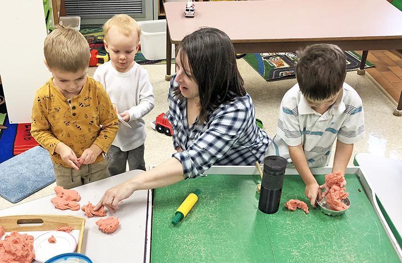 junior kindergartens using playdough with their teacher