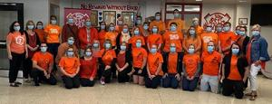 A large group of adults wearing bright orange shirts and medical masks
