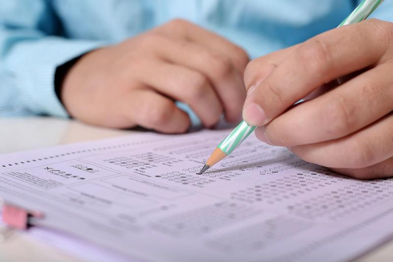 Image of person's hands over top of exam papers