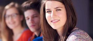 Students looking at the camera, 1 in foreground is clear, two in the background are slightly blurry