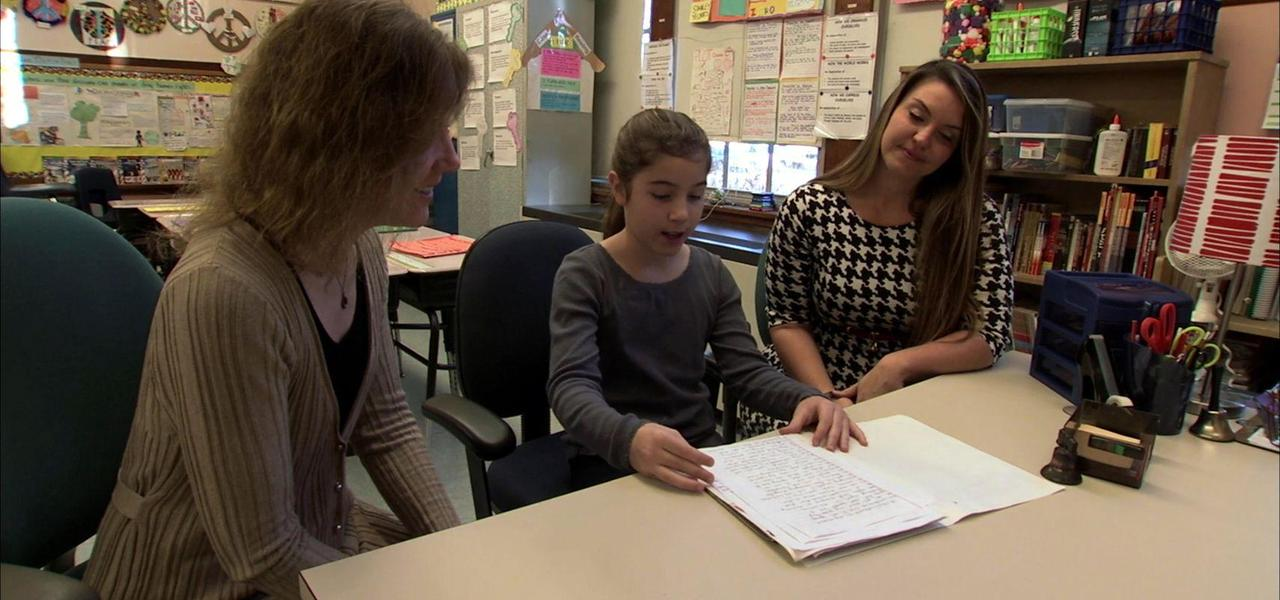 A student showing her work to a parent and teacher