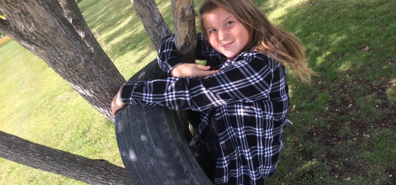 Student sitting in a tire on a tree.