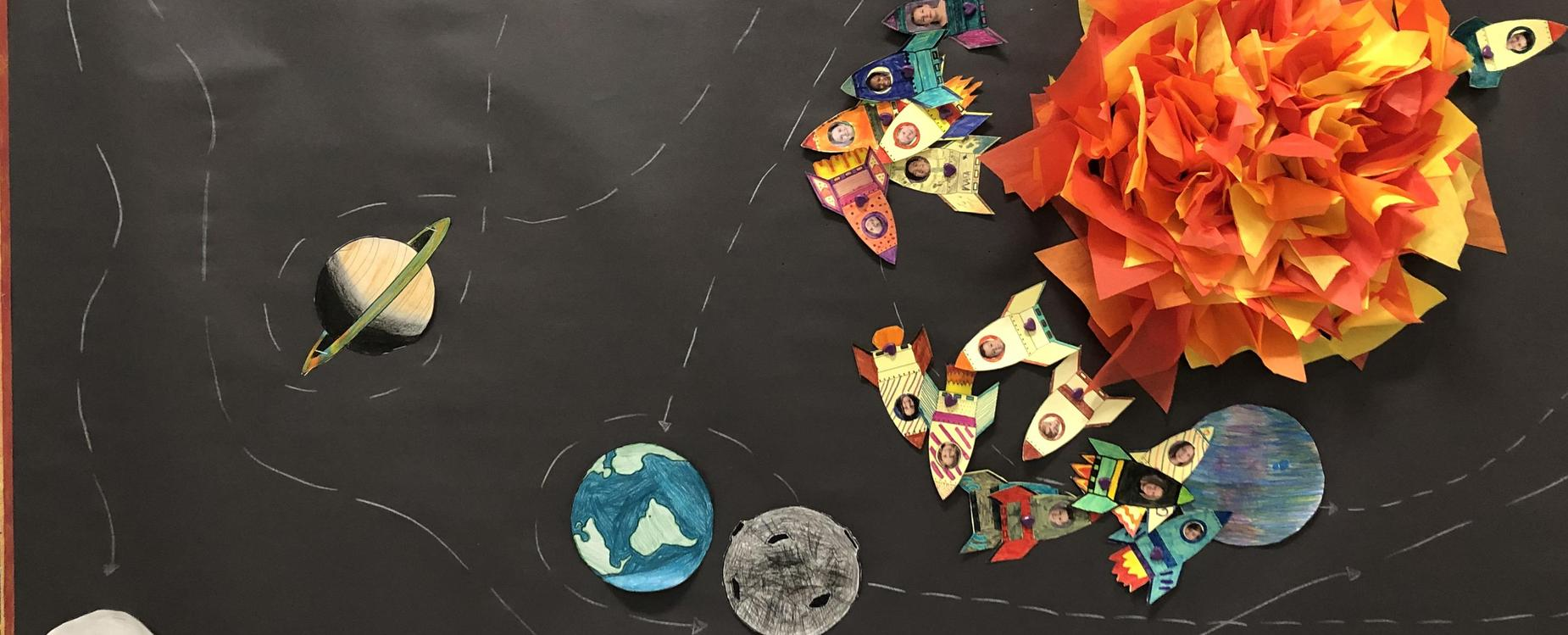 A tissue paper sun on a black background, with planets and student faces in rocketships