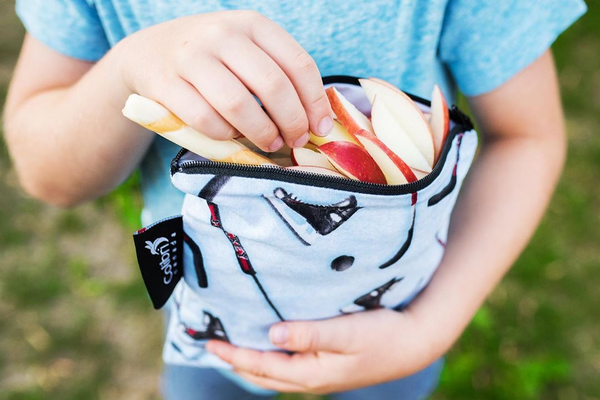 A child holding a cloth snack bag with apple slices