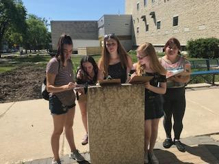 Students at Riel statue plaque