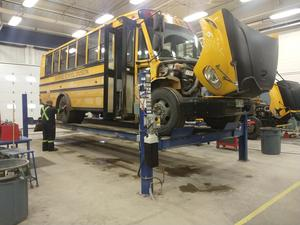 A bus in the Sunrise shop on a lift being worked on.